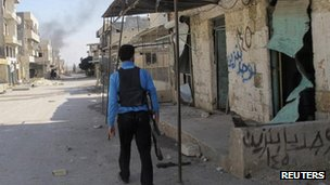 A Free Syrian Army fighter patrols a street in the Taftanaz, 3 Nov