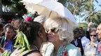 The Duchess of Cornwall is given a kiss by dancer Jenny Lohia as she is presented with a traditional necklace during a visit to Borea village