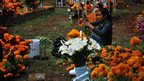 People decorating tombs with flowers for the Day of the dead in Mexico. Photo: Alfredo Leiva