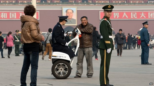 A policeman on a two-wheeled electronic vehicle asking for a man's identity card, other members of the force stand guard around Tiananmen Square in Beijing