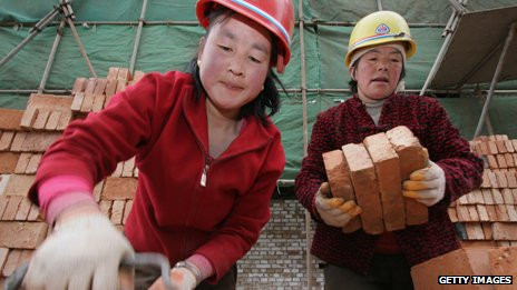 Women migrant workers remove bricks at a construction site on April 5, 2005 in Xining of Qinghai Province, China.