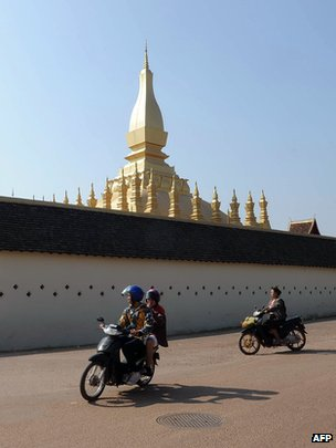 Motorcycle riders in front of the That Luang stupa in Vientiane