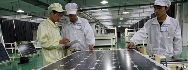 Workers inspecting solar panels at a factory in China