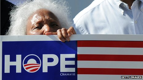 "A woman holding an Obama sign saying ""hope"""