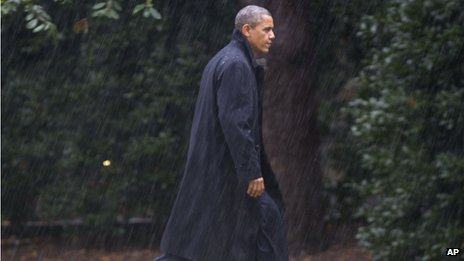After cancelling a rally, President Obama walks through the driving rain