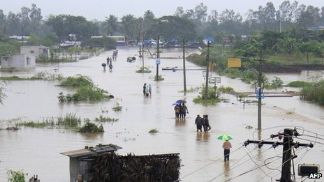 Indian residents wade through flood waters in Visakhapatnam in the coastal district of Andhra Pradesh on November 5, 2012