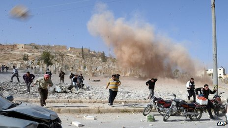 People run for cover after a bomb dropped by a government warplane explodes in the northern Syrian town of al-Bab (4 November 2012)
