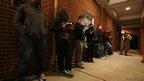 Voters stand in a queue before the polls open at Harrison United Methodist Church