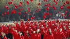 Members of the Chinese Communist Party toss their caps into the air