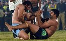 A Pakistani kabaddi player (right) is tackled by his Indian opponent