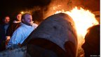 A competitor lifts a flaming wooden barrel