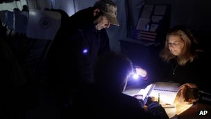 Poll worker Lisa Amico, right, helps voters by flashlight in a dark and unheated tent serving as a polling site in the Midland Beach section of Staten Island, New York, 6 November 2012