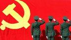 Paramilitary policemen hold their fists in front of a flag of Communist Party of China