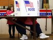 Kaira Ray (left) watches as her grandmother Theresa Bigl votes at the old Town Hall in Bristol, New Hampshire