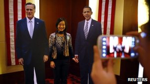 Guests take photo with cardboard cut-outs of President Barack Obama and Republican candidate Mitt Romney at a US election event organised by the US embassy in Beijing, 07 Nov 2012