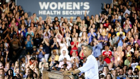 "Obama at a campaign rally in Denver in August 2012, with a big banner saying ""women's health security"""