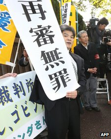 """A supporter of Govinda Prasad Mainali holds a banner which reads """"Not guilty at retrial"""" in front of the Tokyo High Court in Tokyo on 7 November"""