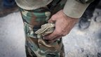 A rebel fighter stuffs a large bundle of notes into his pockets in the northern Syrian city of Aleppo
