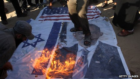 Palestinian Salafists walk on top of a picture of US President Barack Obama while burning Israeli and US flags