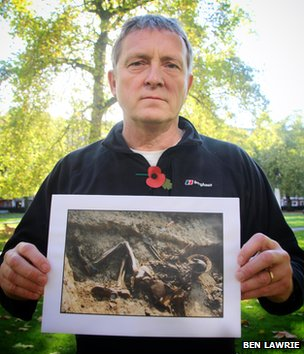 John Hayes Fisher holding a 2001 photograph of a dead WWI soldier