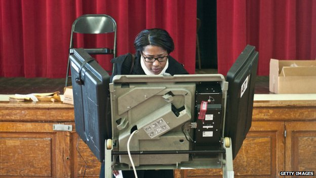 woman stands at electric voting machine