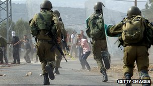 Palestinian protesters throw stones towards Israeli soldiers 