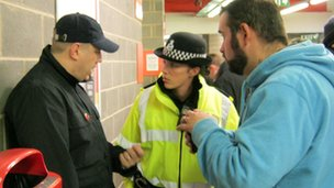Police officer talking to football fans