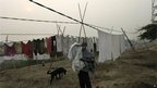 An Indian man carries clothes to dry as the morning sun is enveloped by a blanket of smog, caused by a mixture of pollution and fog in New Delhi, India, Wednesday, Nov. 7, 2012