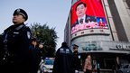 Chinese policemen stand guard near a large screen showing a live broadcast of Chinese President Hu Jintao's remarks at the opening session of the 18th Communist Party congress, in Beijing, 8 November 2012