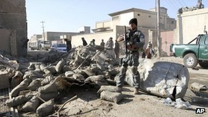 An Afghan policeman stands guard at the scene of a suicide attack in Kandahar, south of Kabul, Afghanistan, Thursday, Nov. 8, 2012.