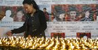 An exiled Tibetan lights butter lamps in front of the portraits of Tibetans who have self-immolated