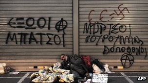 Homesless man sleeping in front of graffiti-covered shuttered shop window (23 Mar 12)