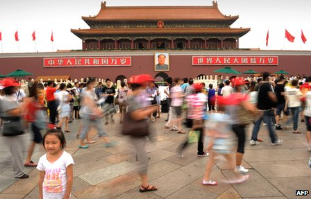 Visitors have their photos taken at Tiananmen gate in Beijing on 17 August 2011