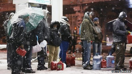People wait in the snow for petrol in Brooklyn, New York 7 November 2012