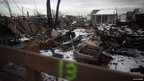 Snow falls on the debris of homes destroyed by a fire sparked by Superstorm Sandy in Breezy Point, New York 8 November 2012