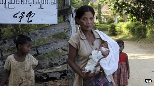 A Rakhine woman carries her baby at a relief camp in Mrauk U, Rakhine state, western Burma, 8 Nov