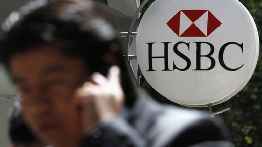 A man talking on a mobile phone walks past a HSBC branch