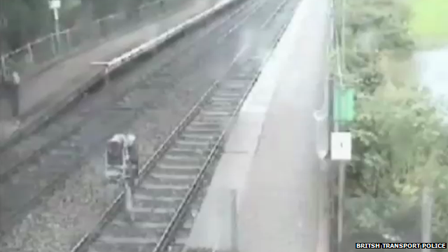 Man carries baby across railway track
