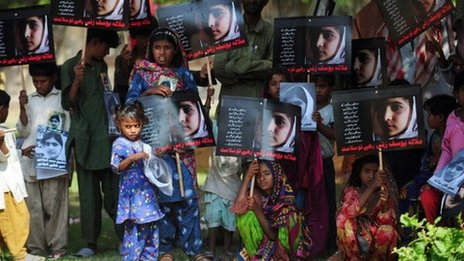 Pakistani flood affected victims carry photographs of child activist Malala Yousafzai to mark the &quot;Malala Day&quot; in Karachi on November 10, 2012