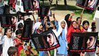 Pakistani flood victims in Karachi, Pakistan carry pictures of Malala Yousafzai as part of Malala Day