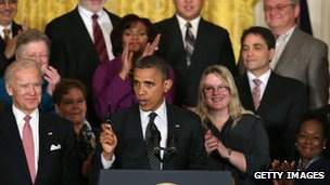 President Barack Obama holds up a pen while speaking to the media in the East Room of the White House on 9 November.
