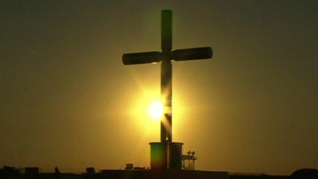 Sun sets behind cross