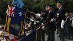 War veteran standard bearers raising flags