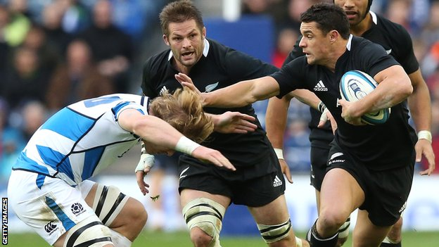 All Blacks fly-half Dan Carter hands off Scotland back rower David Denton