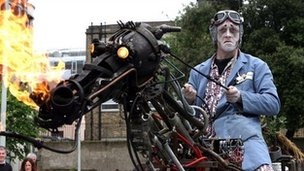 Man dressed in ghoulish costume on a metal horse sculpture
