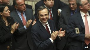Greece's Prime Minister Antonis Samaras and his party's lawmakers of the New Democracy applaud after voting on the country's 2013 budget