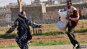 Syrian nationals leave after Syrian aircraft bombed the strategic border town of Ras al-Ain, 12 November 2012
