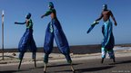 Men on stilts walk before a parade celebrating Cartagena's independence