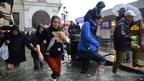People walk in a flooded street in Venice on 11 November 2012