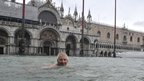 A man swims in a flooded St Mark&#039;s Square in Venice on 11 November 2012